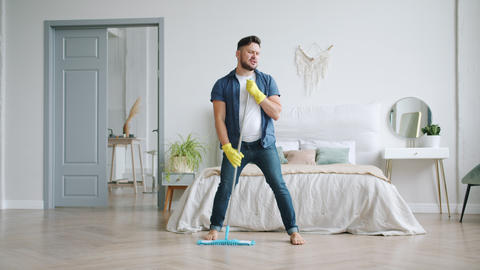 Funny young man singing in mop during clean-up in bedroom having fun alone Footage