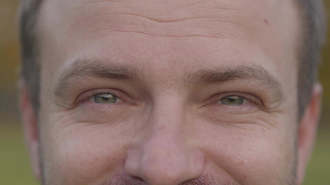 Extreme close-up of an adult caucasian man's grey eyes. Grey-haired guy looking Live Action