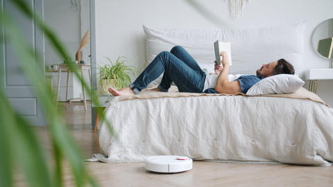 Carefree man reading book in bed while robotic vacuum cleaner vacuuming floor Live Action