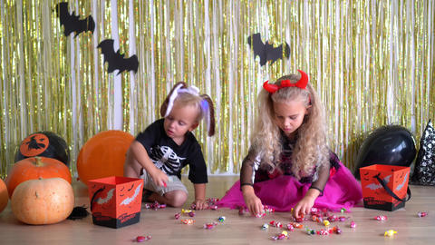 girl and boy take candy from ground together in room decorated for Halloween. 4K GIF