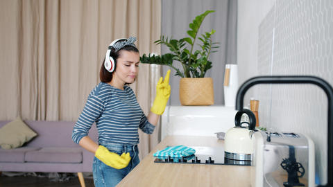 Young woman washing kitchen furniture dancing wearing wireless headphones Footage
