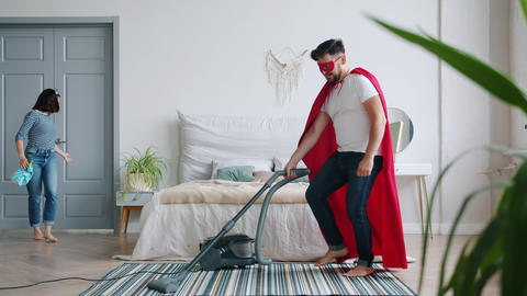 Husband in super hero costume vacuuming floor when wife coming home then running Footage