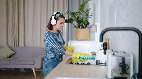 Beautiful girl in headphones cleaning kitchen dancing singing having fun at home Footage