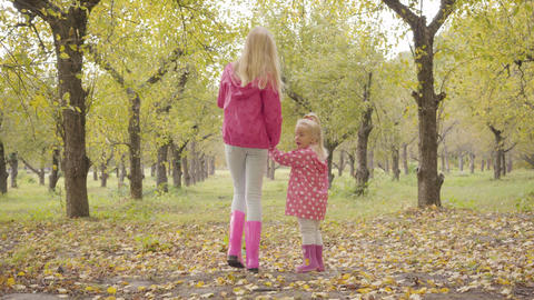 Back view of two blonde girls in pink jackets and pink rubber boots walking in Footage