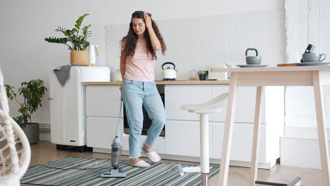 Happy young woman vacuuming carpet in kitchen dancing during clean-up Live Action