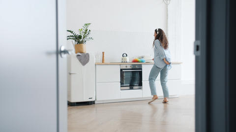 Joyful lady dusting furniture in kitchen and dancing wearing headphones Footage