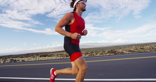 Runner man running in triathlon suit training for Iron man on Hawaii Footage