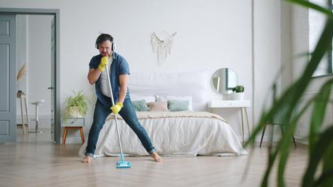 Joyful guy in headphones singing in mop washing floor at home having fun Footage