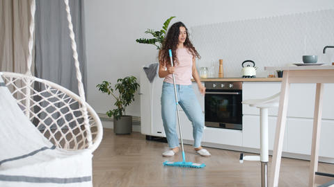 Joyful woman dancing with mop during clean-up in kitchen having fun alone Footage