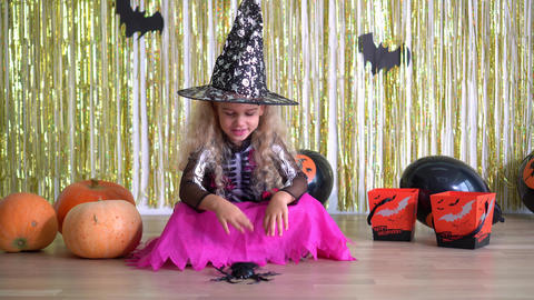 girl with carnival witch dress spell spider. Halloween Witch in magic hat. 4K GIF