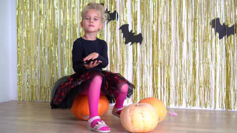 Halloween witch girl hold black spider in hand. pumpkins and horror holiday. 4K Live Action