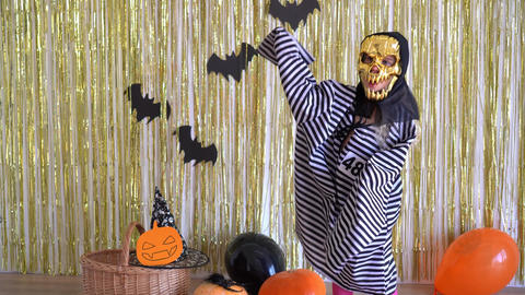 kid with scary Halloween mask and prisoner costume scares from camera. 4K GIF