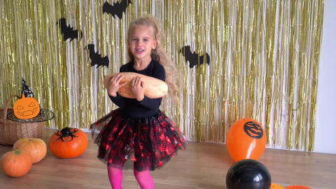 girl in Halloween skirt jumping with pumpkin on glitter decorated background GIF