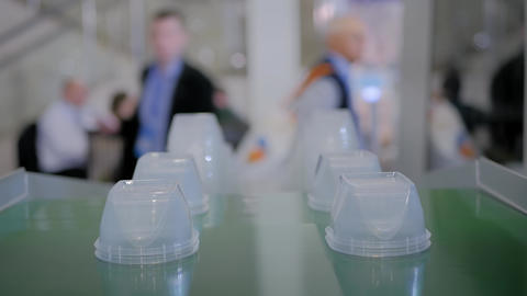 Stack of food containers on conveyor belt of plastic injection molding machine Footage