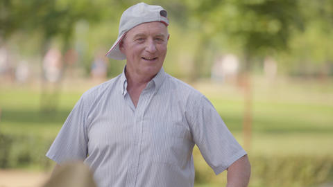 Positive caucasian senior man in white baseball cap dancing in the summer park Footage