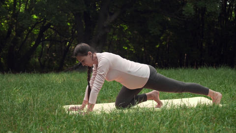 Pregnant woman doing yoga in the park on the carpet, standing on one knee, doing Live Action