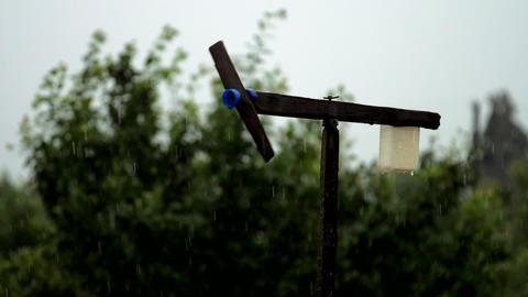 black handmade windmill rotates slowly on rain weather Live Action