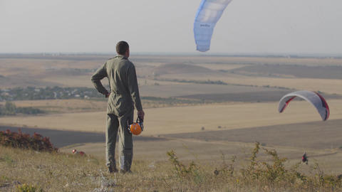 A pilot in overalls with an orange helmet in his hands stands on a hillside and Live Action