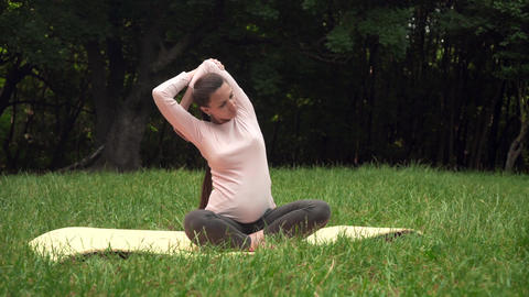 Pregnant woman doing yoga in the park on the carpet, sitting in the lotus Live Action