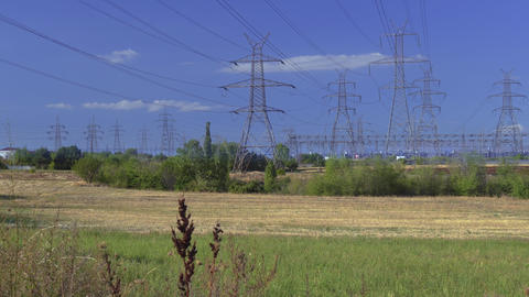 High voltage electric distribution lines on pylons at countryside Live Action