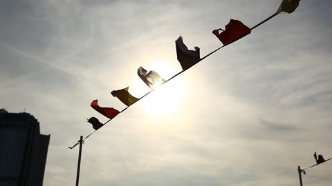 Rope with many small flags flutter on wind against bright sun light and sky Footage