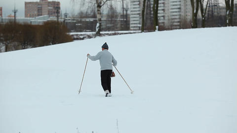 Mature man run ski at snowy slope, city park area, some buildings at backgound Footage