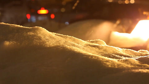 Bright snowdrift lit with yellow, snow flakes slowly fall, blurred car traffic Footage