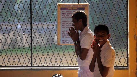 Sinhalese schoolboys pray and boy shows gesture Archivo