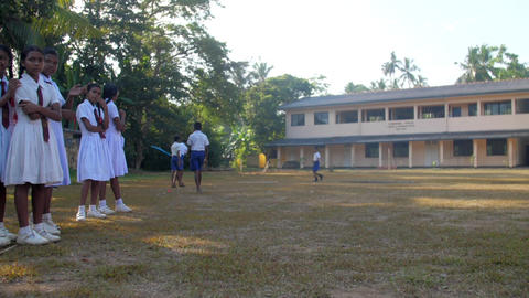 Sinhalese boys play on schoolyard and girls look Archivo