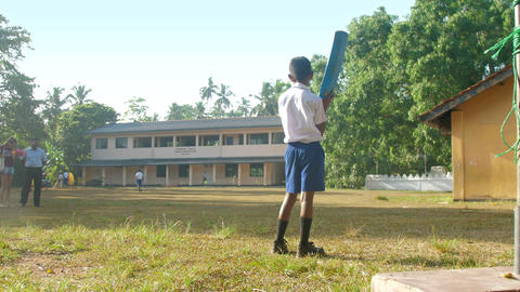 young Sinhalese schoolboy holds blue cricket bat Archivo