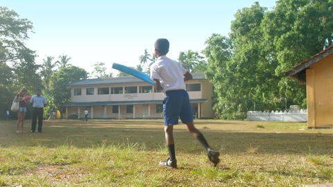 Sinhalese schoolboy holds blue cricket bat and runs Archivo