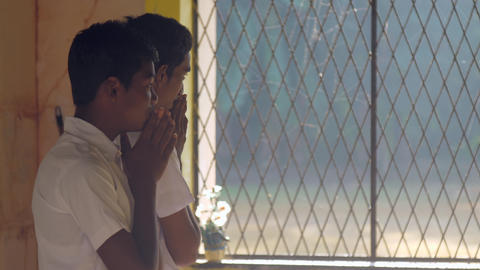 Sinhalese schoolboys pray against large school window Archivo