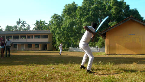 Sinhalese schoolboys in white uniform play cricket Archivo