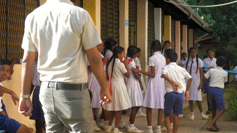 Sinhalese man teacher comes to children in uniforms Archivo