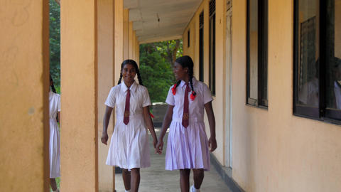 Sinhalese girls walk at green trees near building Archivo