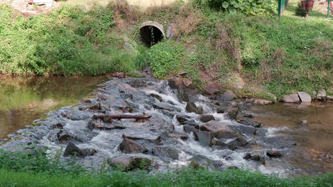 Sewage pipe outflow into river, water pollution and ecology concept Live Action