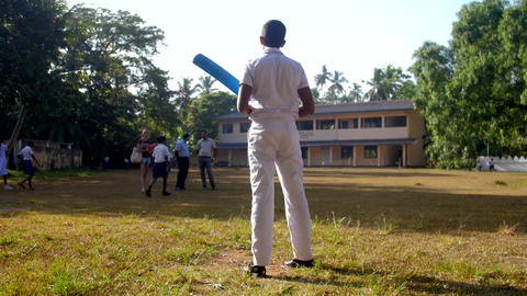 schoolboy stands on green playground holding cricket bat Archivo