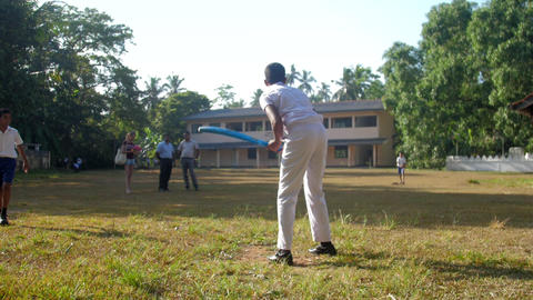 concentrated schoolboy bats flying ball on cricket game Archivo