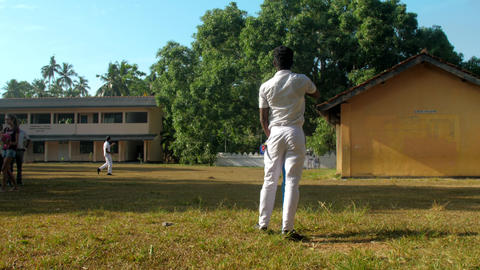 schoolboys in uniform play cricket on schoolyard in autumn Archivo