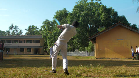 schoolboys play cricket on schoolyard against school Archivo