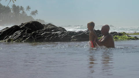 daddy helps son jump in calm sea water at exotic resort Footage