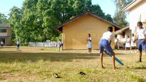 barefoot schoolboy with blue bat misses cricket ball Archivo