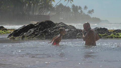 daddy and boy have fun splashing water in tranquil ocean Live Action