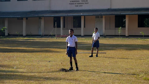 Sinhalese boys on playground against school building Archivo