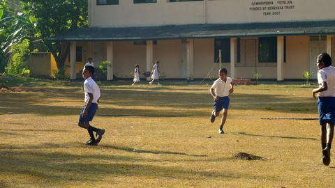 Sinhalese schoolboys run on playground lit by sun Archivo