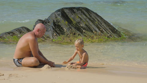 daddy pours wet sand playing with cute son on beach Footage