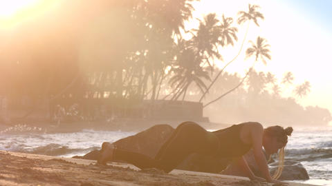 tremendous lady changes yoga position on sandy beach Footage