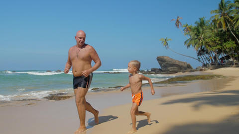 dad and little kid run along exotic ocean coast against sky Footage