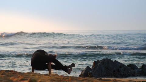 exciting lady stands on hands in yoga position against ocean Footage