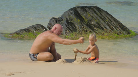 daddy and cute boy build with wet sand on ocean beach Footage